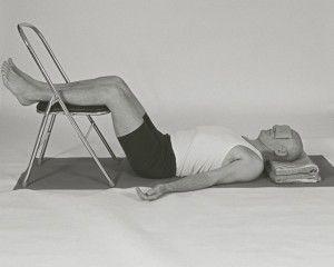 Savasana con silla: permite una profunda relajación mediante la presión en la espalda lumbar.