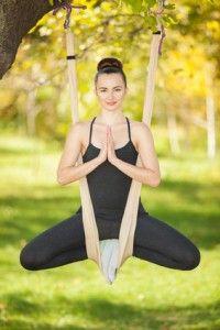 Anti-gravity Yoga, woman doing yoga exercises in the park